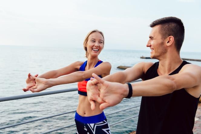 Atractiva pareja joven alegre haciendo estiramientos ejercicios para brazos mientras se ejercita