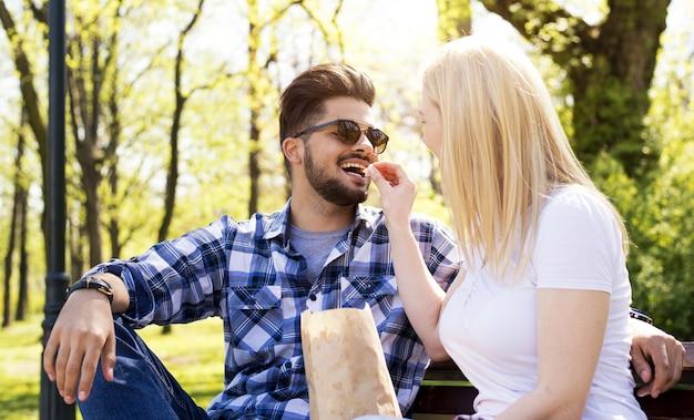 Atractiva pareja joven divirtiéndose y comiendo palomitas de maíz en un banco del parque