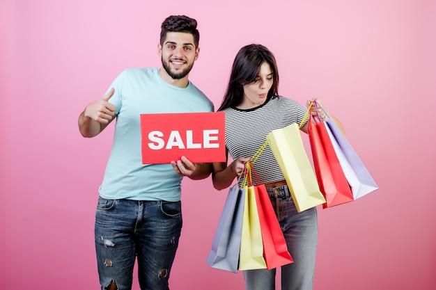 Atractiva pareja joven hombre y mujer con cartel de venta y coloridos bolsos de compras