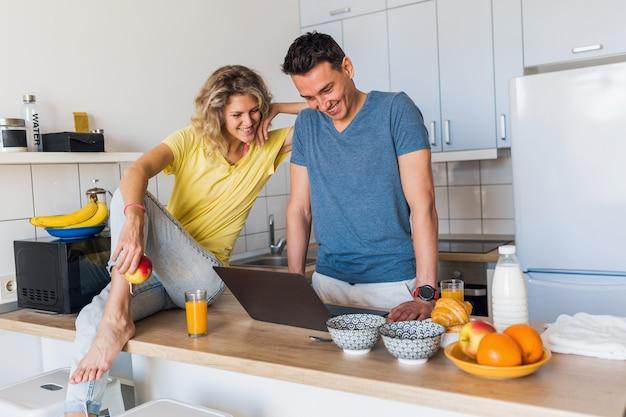 Atractiva pareja joven de hombre y mujer cocinando el desayuno juntos en la mañana en la cocina