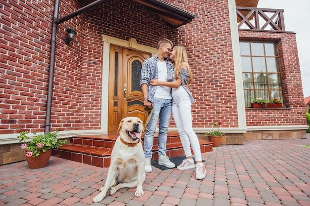 Atractiva pareja joven con labrador frente a su nueva y hermosa casa