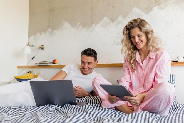 Atractiva pareja joven sentada en la cama por la mañana, leyendo noticias en internet, trabajo autónomo en línea