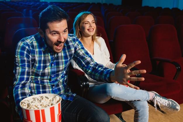 Atractiva pareja joven viendo una película en un cine