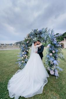 Atractiva pareja de novios enamorados está de pie al aire libre cerca del hermoso arco hecho de flores azules