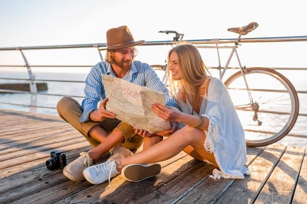 Atractiva pareja sonriente feliz viajando en verano por mar en bicicleta