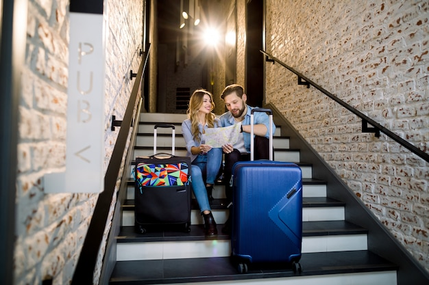 Atractiva pareja sonriente de hombre y mujer en elegante estilo casual de negocios con dos maletas, sentados en las escaleras en el elegante vestíbulo del hotel tipo loft en el interior, mirando juntos en el mapa de la ciudad