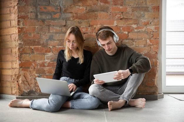 Atractiva pareja sorprendida y asombrada usando dispositivos juntos