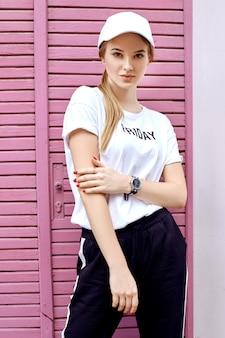 Atractiva rubia vestida con una gorra blanca, camiseta y pantalones camina por la calle cerca de la pared rosa en un día de verano