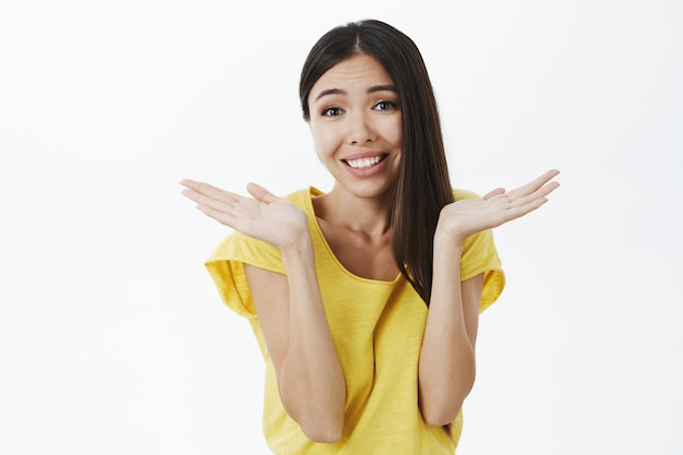 Atractiva tonta encantadora mujer de cabello oscuro con piel bronceada y sin maquillaje encogiéndose de hombros con las manos cerca de los hombros sonriendo ampliamente