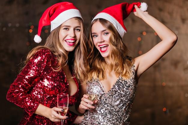 Atractivas mujeres bien vestidas disfrutando de la navidad juntos