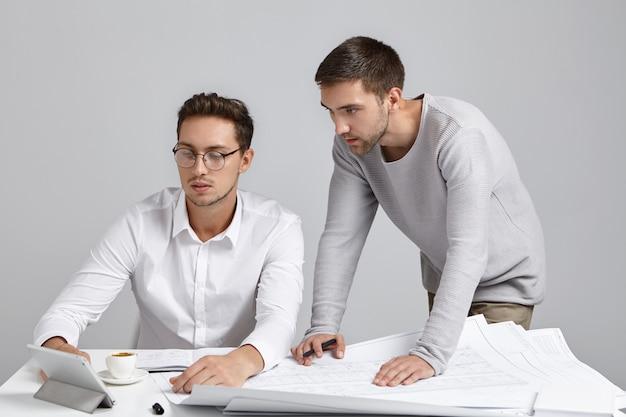 Atractivo arquitecto masculino enseña a su aprendiz masculino, explica los detalles del trabajo en tableta, toma un café