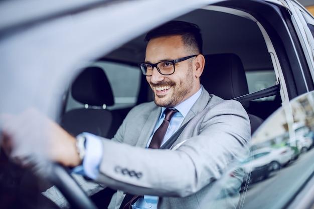 Atractivo caucásico sonriente elegante empresario sin afeitar en traje y anteojos conduciendo su coche caro.
