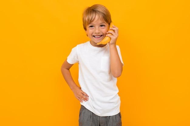 Atractivo chico europeo en una camiseta blanca hablando en un plátano como en el teléfono en una pared naranja