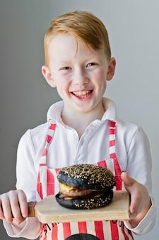 Un atractivo chico pelirrojo sostiene una tabla de cortar de madera con una hamburguesa.