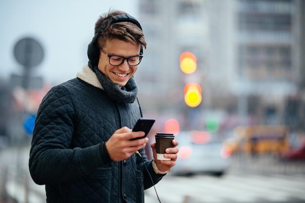 Atractivo chico sonriente escuchando música en auriculares, usando su teléfono móvil