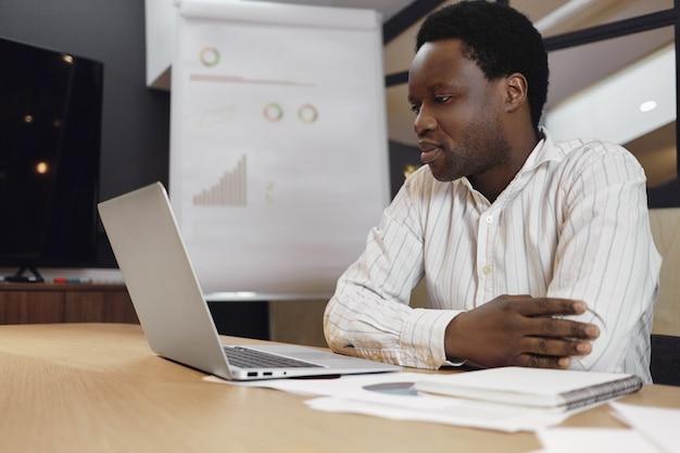 Atractivo empresario afroamericano serio en camisa a rayas trabajando