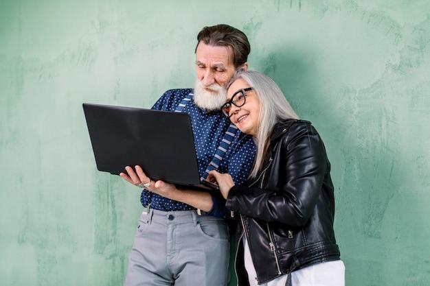 Atractivo feliz pareja senior elegante, hombre y mujer, apoyándose en la pared verde y abrazándose, mientras usa la computadora portátil, disfrutando del tiempo juntos