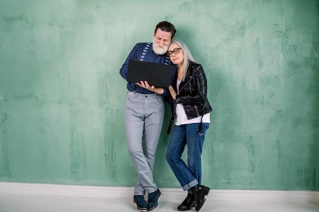 Atractivo feliz pareja senior moderna, hombre y mujer, vistiendo ropa elegante de moda, parados juntos cerca de la pared verde, apoyándose mutuamente y usando una computadora portátil