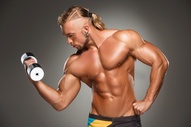 Atractivo fisicoculturista masculino en pared gris