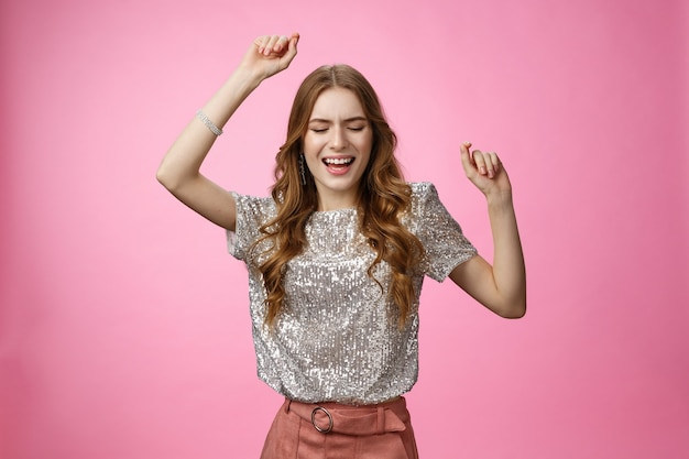 Atractivo glamour mujer bailando pista de baile divirtiéndose rase manos arriba cielo ojos cerrados cantando a lo largo de s ...