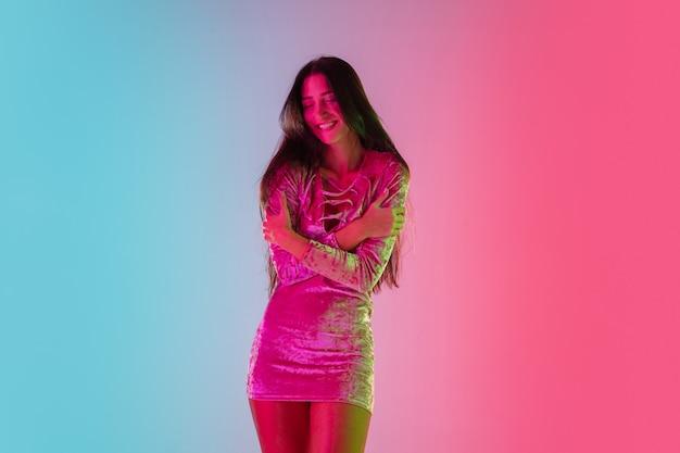 Atractivo. hermosa chica seductora en vestido de moda, traje sobre fondo rosa-azul degradado en luz de neón. retrato de medio cuerpo. copyspace para anuncio. verano, moda, belleza, concepto de emociones.