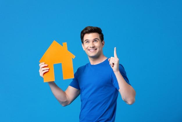 Atractivo hombre americano guapo sosteniendo un modelo de vivienda