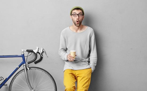 Atractivo hombre asombrado vendiendo bicicleta deportiva, tomando café de una taza para llevar, mirando con gran sorpresa al notar a muchos clientes. hombre sin afeitar que tiene parada después de andar en bicicleta en la calle