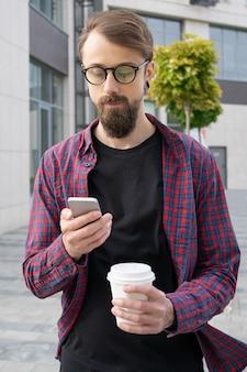 Atractivo hombre barbudo en anteojos con smartphone