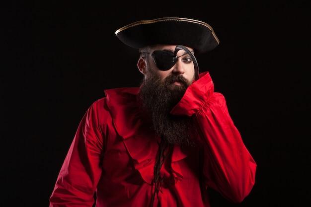 Atractivo hombre barbudo con un disfraz de pirata para carnaval tocando su parche en el ojo con su gancho de brazo. hombre disfrazado de halloween.
