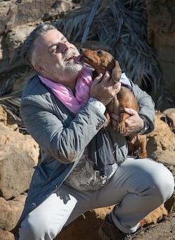 Atractivo hombre barbudo en la orilla del mar con perro salchicha, perro
