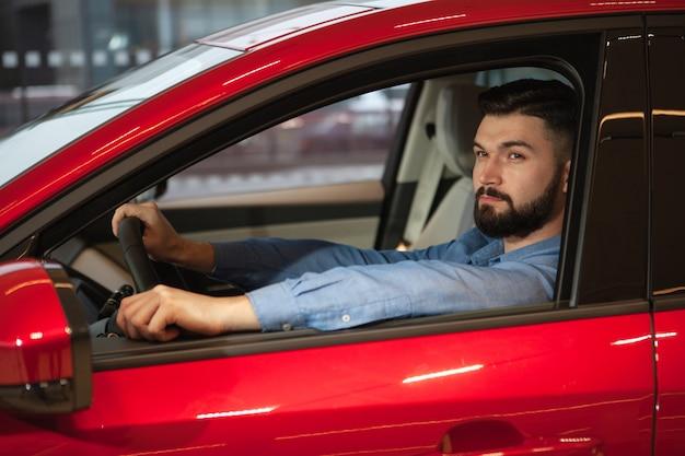 Atractivo hombre barbudo sentado en un automóvil nuevo en el concesionario