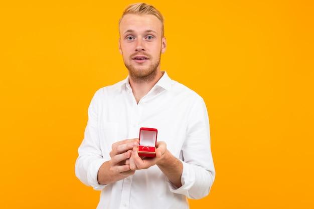 Atractivo hombre europeo rubio hace una propuesta con un anillo en una caja sobre un fondo amarillo.