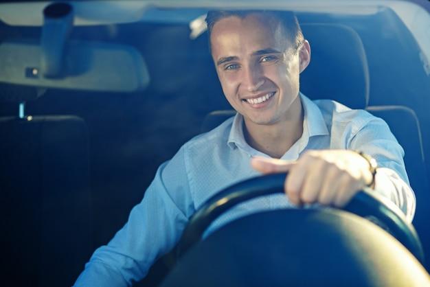 Atractivo hombre exitoso guapo en camisa blanca conduciendo un coche caro