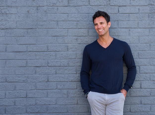 Atractivo hombre mayor sonriendo contra la pared gris
