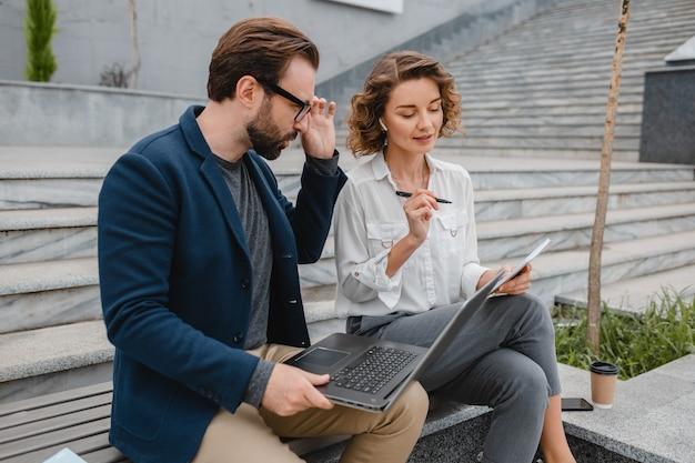 Atractivo hombre y mujer sonriente hablando sentado en un banco en el centro urbano de la ciudad, tomando notas