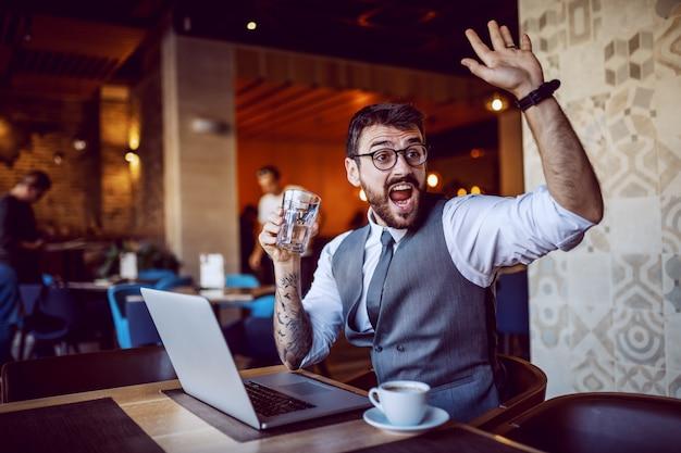 Atractivo hombre de negocios caucásico barbudo en traje y con anteojos sosteniendo un vaso de agua y saludando mientras está sentado en la cafetería. en la mesa hay una computadora portátil y una taza de café.