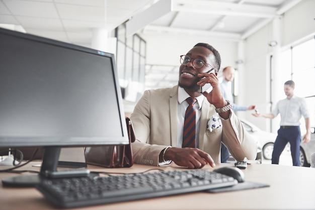Atractivo hombre de negocios negro se sienta a la mesa en el concesionario de automóviles, firma un contrato y compra un automóvil nuevo.