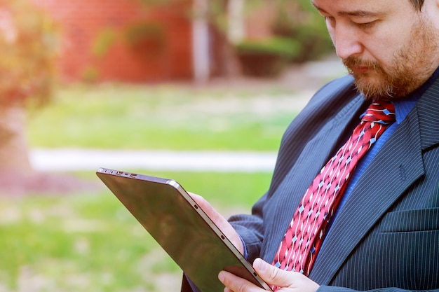 Atractivo hombre de negocios en traje y corbata con tableta digital al aire libre trabajando en edificios de oficinas exteriores