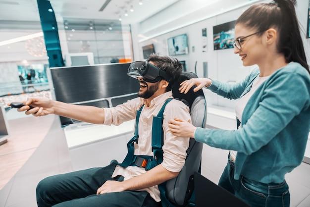 Atractivo hombre de raza mixta con barba que intenta tecnología de realidad virtual mientras la mujer mira lo que está haciendo. interior de la tienda de tecnología.