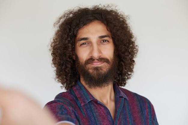 Atractivo hombre rizado morena positiva con barba sonriendo sinceramente mientras hace selfie, vistiendo camisa a rayas multicolor