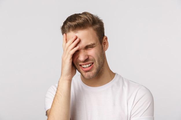 Atractivo hombre rubio con barba en camiseta blanca con dolor de cabeza