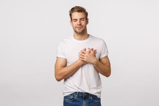 Atractivo hombre rubio con barba en camiseta blanca con las manos en el corazón