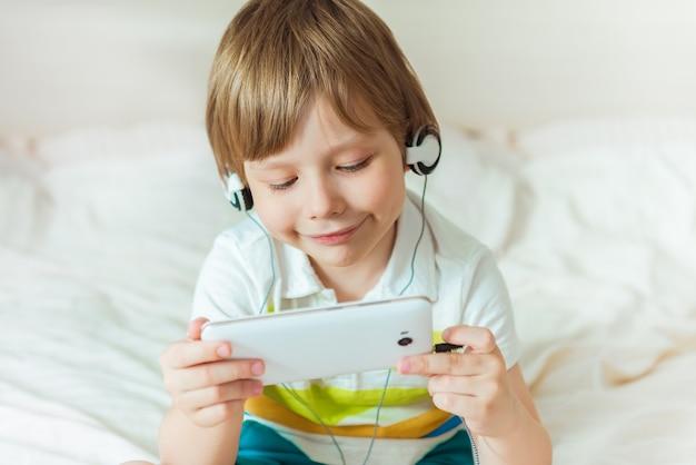 Atractivo joven adolescente acostado en la cama sonriendo y mirando a la computadora portátil charlando con amigos. navegar en línea, enviar mensajes o trabajar desde casa