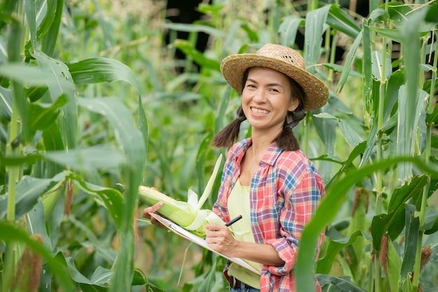 Atractivo joven agricultor sonriendo de pie en el campo de maíz en primavera