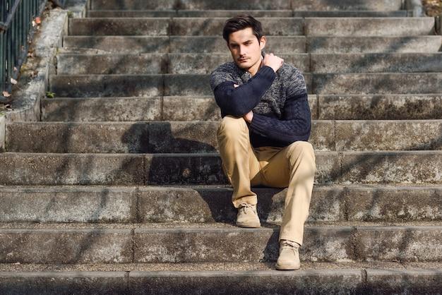 Atractivo joven apuesto hombre, el modelo de la moda en el fondo urbano