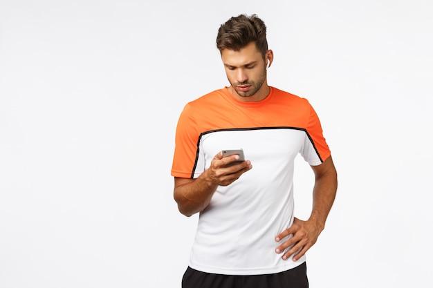 Atractivo joven atleta masculino en camiseta deportiva, correr, prepararse para el maratón