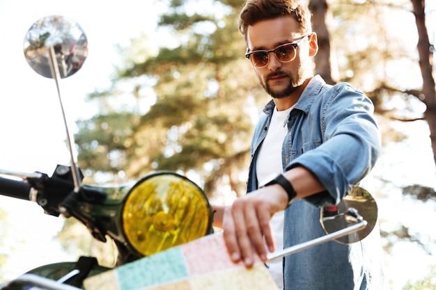Atractivo joven barbudo cerca de scooter mirando el mapa