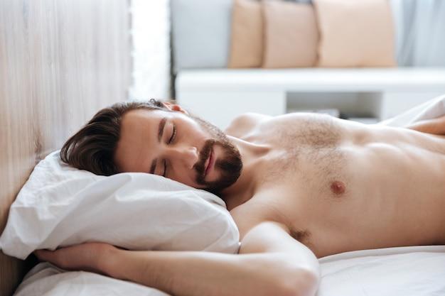 Atractivo joven barbudo durmiendo en la cama