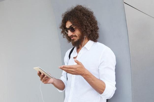 Atractivo joven barbudo hombre rizado de pelo oscuro apoyado en una pared exterior gris durante el video chat con tableta, con gafas de sol y ropa casual