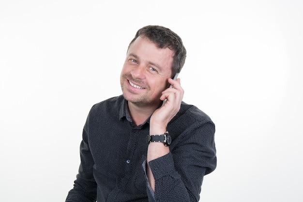 Atractivo joven en camisa negra hablando por su teléfono celular